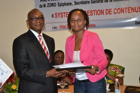 Edith Brou, recevant des mains de M. Eric Contayon, conseiller technique au Ministère de la Poste et TIC, son diplôme de participation
